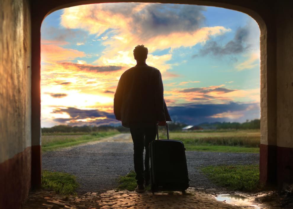 man with suitcase heading into horizon